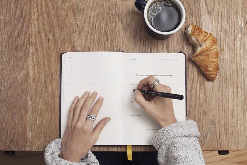 手帳に文字を書いている女性の手