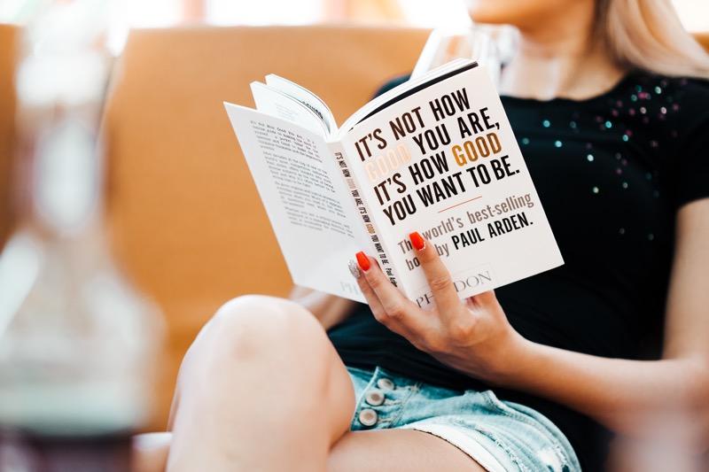 片手で本を読む女性